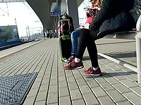 Candid girl wearing new balance sneakers waiting for a tain