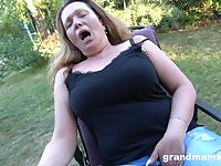 the mature using her fingers to finger her wet pussy in the garden